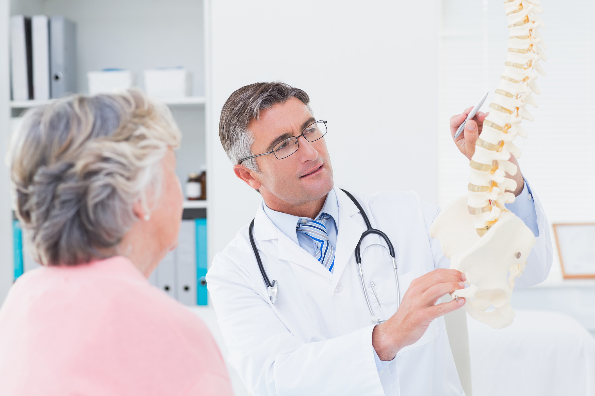 Doctor using a model of spine to explain condition to patient